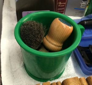 Ed Bankston uses this single, plastic mug and its contents to give his customers a traditional hot shave.  In the early 20th century, each customer had his own mug placed in a cabinet belonging to the barber. (photo by Joanne Wyant)