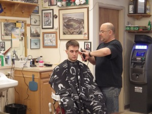 Jason Fabick, co-owner of Jason's Barbershop located in Downtown Kent's Acorn Alley puts some finishing touches on a trim.  Jason's is known for its friendly atmosphere and huge collection of sports memorabilia.